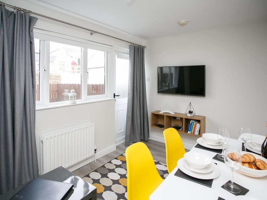 The Wee Snug dining table and a flat TV