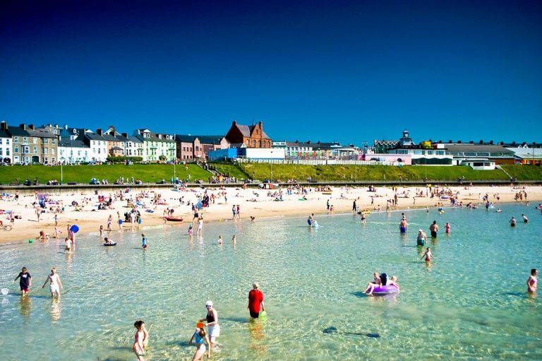 Portrush West Strand Beach on a summers day with lots of people playing in the sea